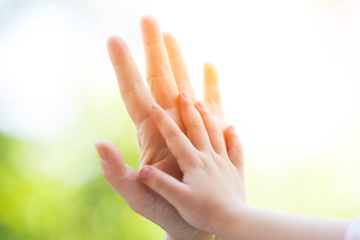 Mother and child with palm to palm hands